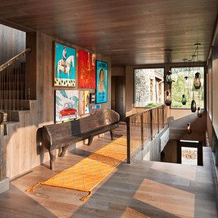 Réalisation d'un grand couloir chalet avec un sol en bois brun, un mur marron et un sol marron.