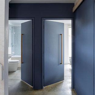 グロスタシャーの中くらいのコンテンポラリースタイルのおしゃれな廊下 (青い壁、コンクリートの床) の写真