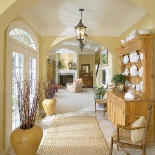 Идея дизайна: большой коридор в классическом стиле с желтыми стенами и полом из травертина