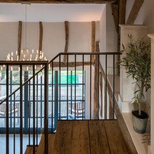 バッキンガムシャーの広いカントリー風おしゃれな廊下 (白い壁、セラミックタイルの床、白い床) の写真