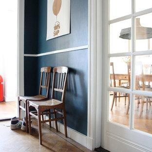 Idéer för eklektiska hallar, med blå väggar och mellanmörkt trägolv