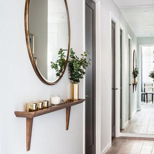 Esempio di un piccolo ingresso o corridoio minimal con pareti bianche, pavimento in legno massello medio e pavimento marrone