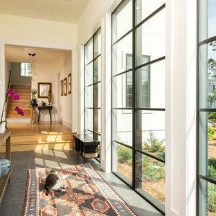 Idée de décoration pour un couloir champêtre avec un mur blanc et un sol gris.