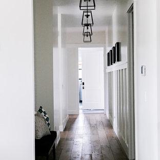Imagen de recibidores y pasillos de estilo de casa de campo, de tamaño medio, con paredes blancas, suelo de madera en tonos medios y suelo marrón