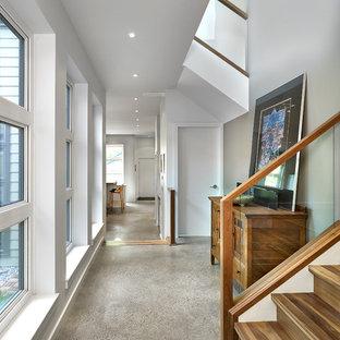 Modern inredning av en mellanstor hall, med grått golv, grå väggar och betonggolv