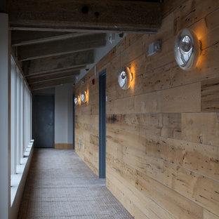 Пример оригинального дизайна: большой коридор в стиле рустика с коричневыми стенами, ковровым покрытием, серым полом и деревянными стенами