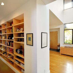 Inspiration pour un grand couloir design avec un mur blanc, un sol en bois brun et un sol jaune.