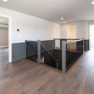 Bild på en amerikansk hall, med grå väggar, mellanmörkt trägolv och brunt golv