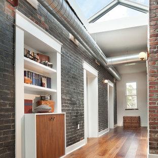 Idee per un ingresso o corridoio industriale di medie dimensioni con pareti nere e pavimento in legno massello medio