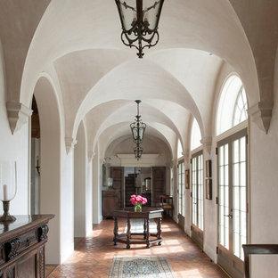 Diseño de recibidores y pasillos tradicionales con paredes beige y suelo de baldosas de terracota