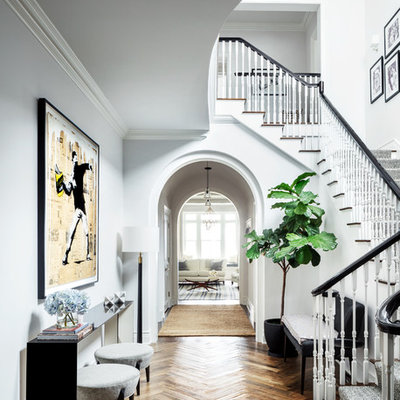 Example of a classic medium tone wood floor and brown floor hallway design in New York with white walls