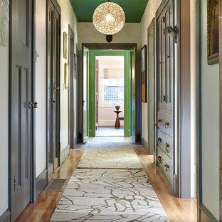 Foto di un ingresso o corridoio tradizionale con pareti bianche e pavimento in legno massello medio