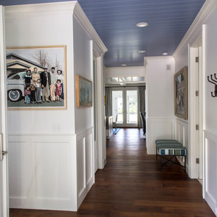 Mid-sized beach style hallway in Grand Rapids with white walls, dark hardwood floors and brown floor.