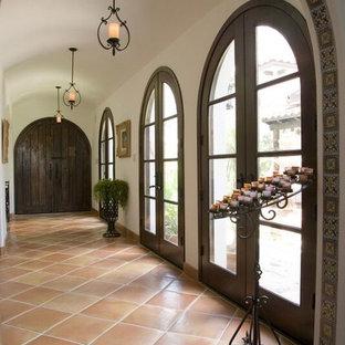 ヒューストンの中サイズの地中海スタイルのおしゃれな廊下 (ベージュの壁、テラコッタタイルの床、茶色い床) の写真