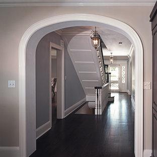 Идея дизайна: большой коридор в стиле неоклассика (современная классика) с бежевыми стенами, темным паркетным полом и черным полом