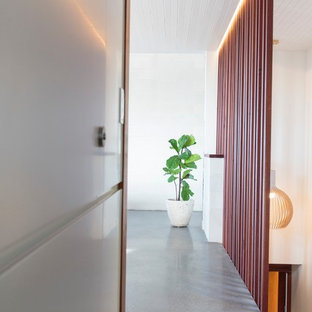 Photo of a mid-sized beach style hallway in Newcastle - Maitland with white walls, concrete floors and grey floor.