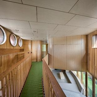 Modern inredning av en mellanstor hall, med gula väggar, heltäckningsmatta och grönt golv