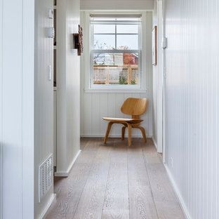 Inspiration for a beach style medium tone wood floor hallway remodel in Boston with white walls