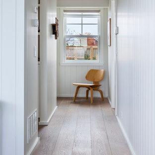 Cette photo montre un couloir bord de mer avec un mur blanc et un sol en bois brun.
