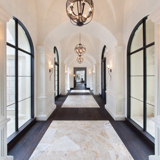 Réalisation d'un très grand couloir tradition avec un mur blanc, un sol en bois foncé et un sol multicolore.