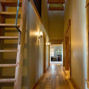 Inspiration pour un couloir chalet avec un mur beige, un sol en bois brun et un sol jaune.