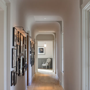 Example of a classic medium tone wood floor hallway design in Austin with white walls