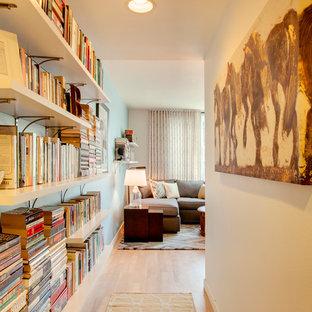 Ejemplo de recibidores y pasillos tradicionales renovados con paredes blancas y suelo de madera en tonos medios