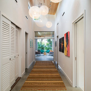 Example of a 1960s concrete floor hallway design in Tampa with white walls