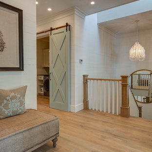 This is an example of an expansive beach style hallway in Atlanta with white walls, light hardwood floors and beige floor.