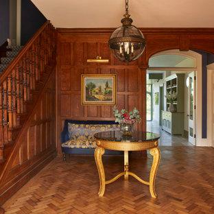 Свежая идея для дизайна: большой коридор в классическом стиле с синими стенами, паркетным полом среднего тона, коричневым полом и панелями на части стены - отличное фото интерьера