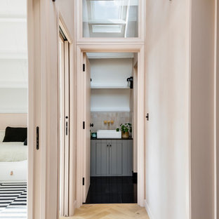 Inspiration for an industrial light wood floor hallway remodel in London with pink walls