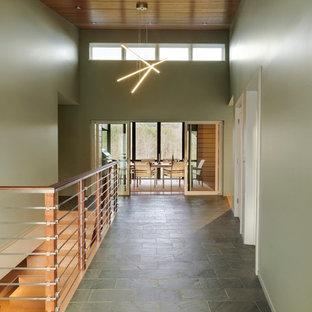 Cette image montre un grand couloir vintage avec un mur vert et un sol en ardoise.