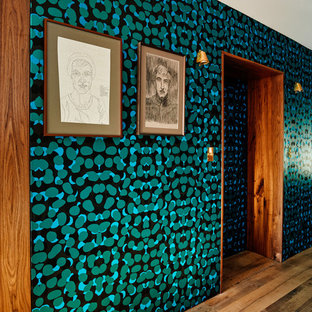 Trendy medium tone wood floor hallway photo in New York with multicolored walls