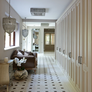 Example of a mid-sized ornate ceramic floor hallway design in London with white walls