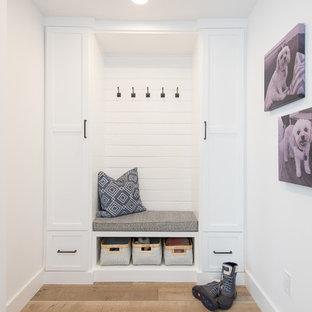 Exemple d'un couloir nature de taille moyenne avec un mur blanc, un sol en bois brun et un sol marron.