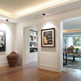 Inspiration för en mellanstor funkis hall, med vita väggar och mellanmörkt trägolv