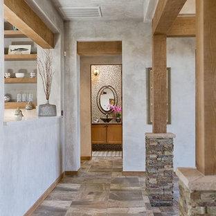 Cette photo montre un grand couloir sud-ouest américain avec un mur beige et un sol en carrelage de porcelaine.