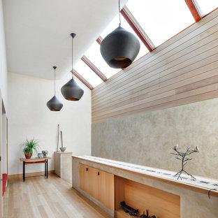 Inredning av en modern hall, med vita väggar, ljust trägolv och beiget golv