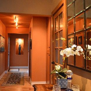 Idee per un piccolo ingresso o corridoio tradizionale con pareti arancioni, parquet chiaro e pavimento arancione