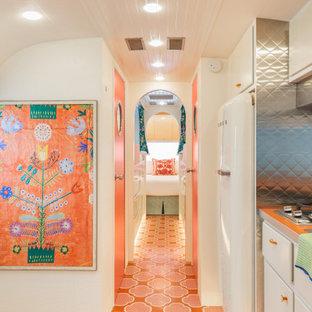 Идея дизайна: маленький коридор в стиле фьюжн с белыми стенами, деревянным полом и оранжевым полом