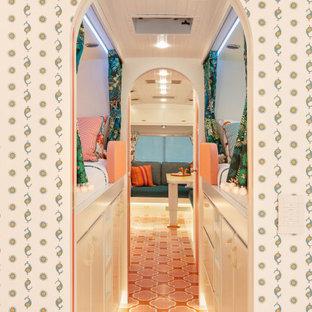 Inspiration för små eklektiska hallar, med vita väggar, målat trägolv och orange golv