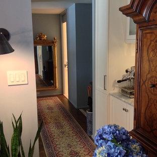 Immagine di un piccolo ingresso o corridoio chic con pareti blu e pavimento in legno massello medio