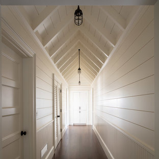 Large beach style hallway in Providence with white walls, dark hardwood floors and brown floor.