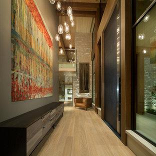 Idée de décoration pour un très grand couloir minimaliste avec un mur gris et un sol en bois clair.