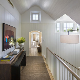 Photo of a mid-sized beach style hallway in Boston with white walls and medium hardwood floors.