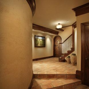 Inspiration pour un couloir traditionnel avec un mur beige et un sol rouge.