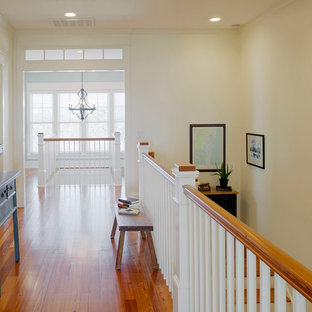 This is an example of a large beach style hallway in Charleston with white walls and medium hardwood floors.