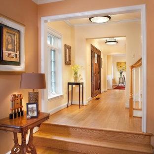 На фото: коридор в классическом стиле с оранжевыми стенами и паркетным полом среднего тона с