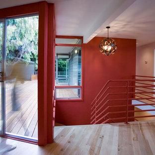 Esempio di un ingresso o corridoio design con pareti rosse e parquet chiaro
