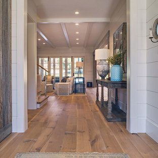 Example of a farmhouse medium tone wood floor hallway design in Atlanta with white walls